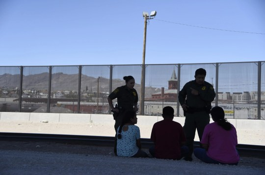 Border Patrol Agents Sara Cabrera, left, and Mario Escalante detain a mother and her two children along the El Paso and Juarez, Mexico on June 24, 2019. The family says they have traveled from El Salvador.