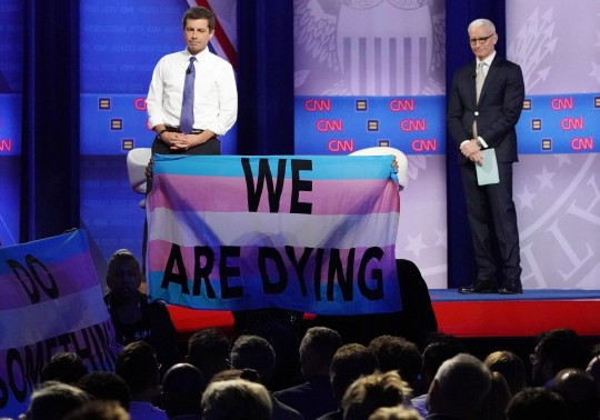LOS ANGELES, CALIFORNIA - OCTOBER 10: Democratic presidential candidate South Bend, Indiana Mayor Pete Buttigieg (L) and CNN moderator Anderson Cooper react as protestors display banners at the Human Rights Campaign Foundation and CNNs presidential town hall focused on LGBTQ issues on October 10, 2019 in Los Angeles, California. It is the first Presidential event broadcast on a major news network focused on LGBTQ issues. (Photo by Mario Tama/Getty Images) ORG XMIT: 775317371 ORIG FILE ID: 1180316273