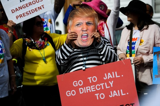 Susan Coe wears a Donald Trump mask and prison attire during a protest against the President speaking at Benedict College Friday, Oct. 25, 2019.
