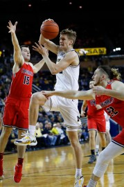 Michigan guard Cole Bajema (22) rolls on James Toohey of Saginaw Valley State (15), Australia, during the first half of an NCAA basketball game in Ann Arbor, Michigan, Friday November 1, 2019.