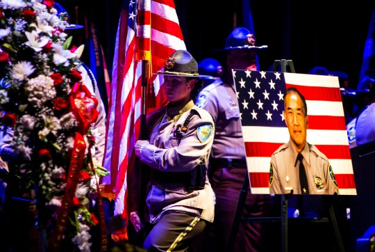 """MCSO officers march with a flag in respect of fallen detention Officer Gene """"Jim"""" Lee during the public celebration of life service for Maricopa County Sheriff's Office Officer Gene """"Jim"""" Lee, who was fatally attacked by an inmate at Lower Buckeye Jail, at Comerica Theater on Friday, Nov. 8, 2019."""
