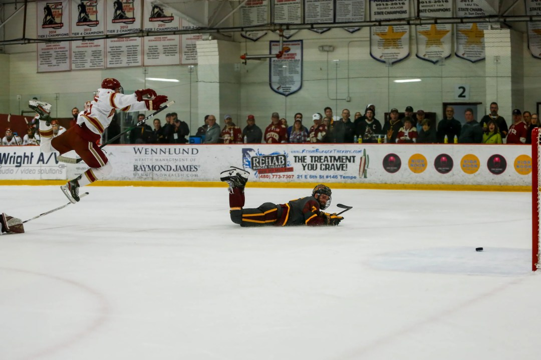 Denver Pioneers defenseman Ian Mitchell (15) falls over Denver Pioneers goaltender Filip Larsson (30)'s stick as Arizona State Sun Devils forward Johnny Walker (7)'s shot slides into the goal in the first period of the Arizona State Sun Devils game against the Denver Pioneers Friday, December 6, 2019 at Oceanside Ice Arena in Tempe.