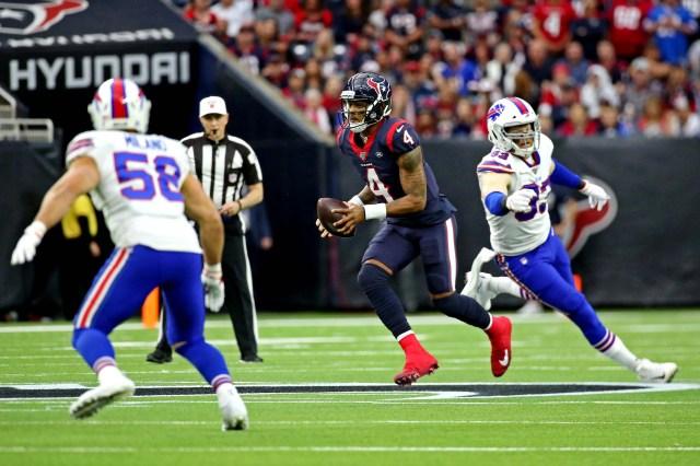 Houston Texans quarterback Deshaun Watson (4) runs the ball against Buffalo Bills defensive back Siran Neal (33) and outside linebacker Matt Milano (58) during the first quarter in the AFC wild-card playoff game at NRG Stadium.