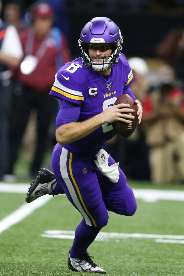 Vikings quarterback Kirk Cousins rolls out to pass during the first quarter.