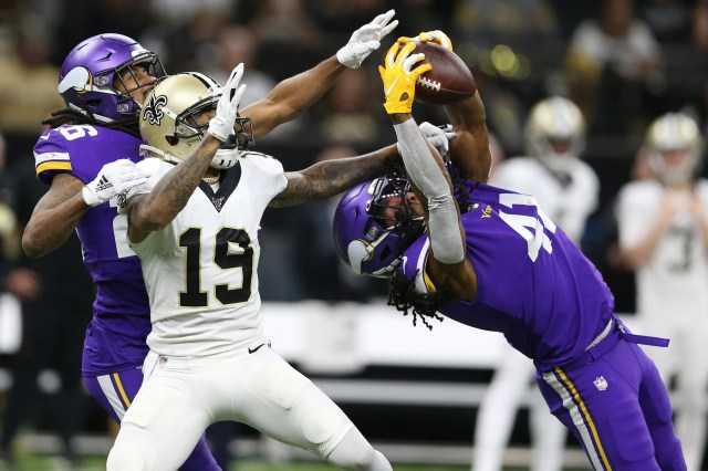 Vikings defensive back Anthony Harris intercepts a pass intended for Saints wide receiver Ted Ginn.