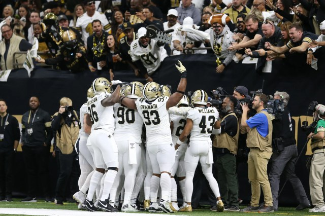 Saints players celebrate with fans after recovering a fumble in the first quarter.