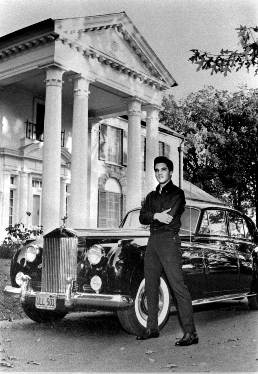 Elvis Presley poses in front of his home with his Rolls Royce in October 1960. Back home after a stint of movie-making in Hollywood, Elvis proudly posed with the latest mark of his fame: a brand-new black Standard Salon Silver Cloud II Rolls Royce worth around $18,000.