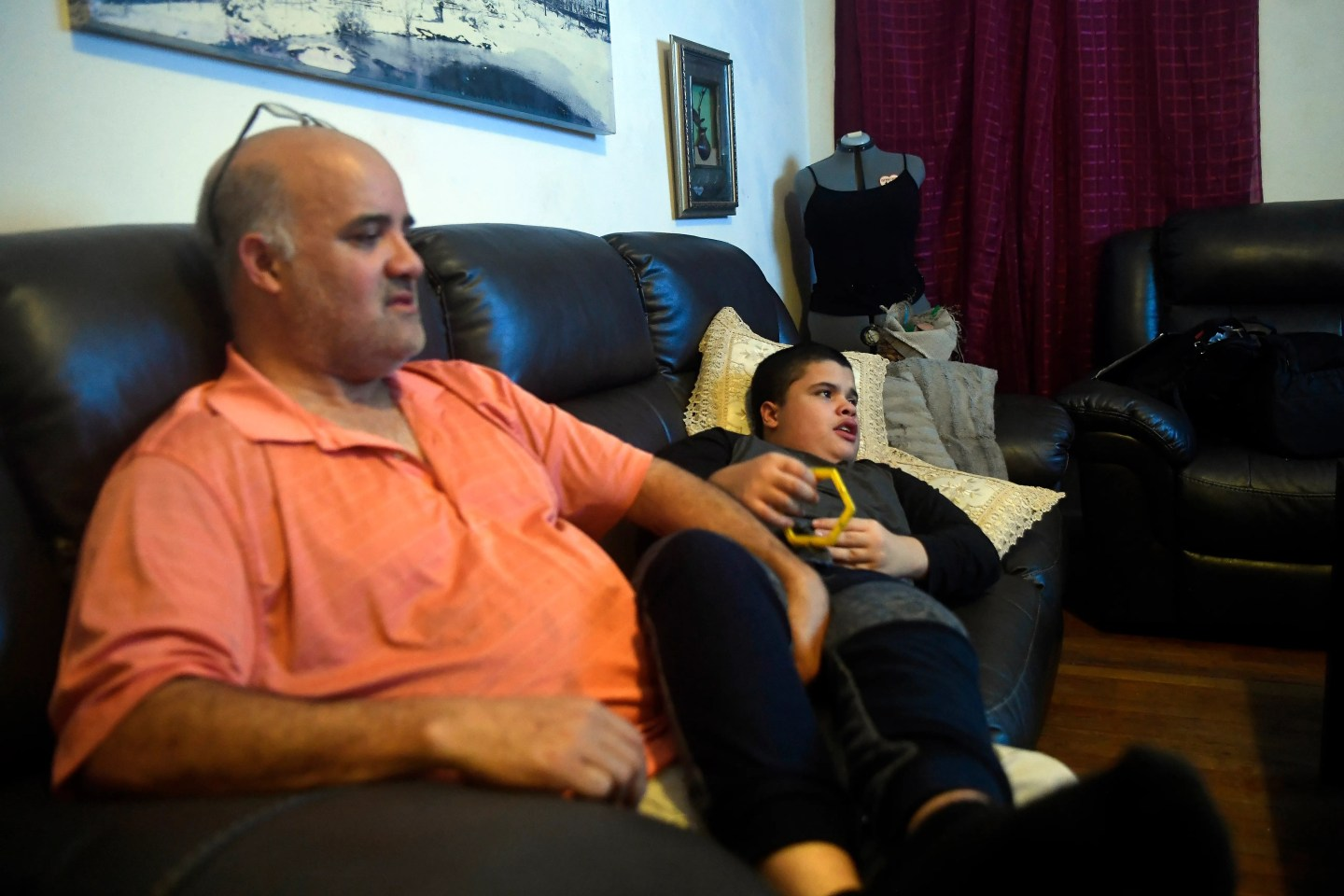 Henry Tejada watches TV with his son Carlos on Jan. 13, 2020.