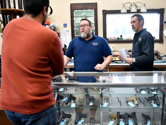 Rick Brubaker, center, and Jeff Rodemyer help a first-time gun buyer with his handgun selection at Bluestone Firearms in Lower Windsor Towship, Tuesday, March 17, 2020. John A. Pavoncello photo