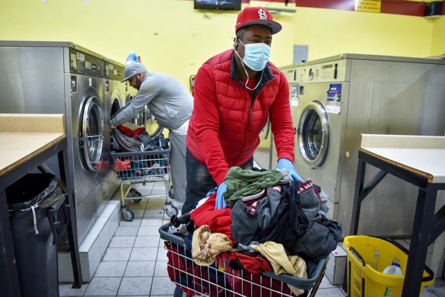 Daily routines must continue, Sammy Irizarry of Passaic, wears a mask and gloves as a precaution against COVID-19 while washing his clothes at Tri-City Laundromat on Sunday, March 22, 2020. Irizarry has preexisting health conditions, including diabetes and high blood pressure and is still working.