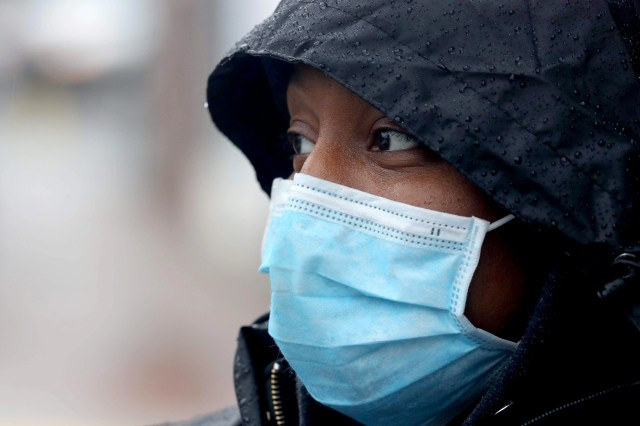 Mail carrier Jasmine Armstrong wears a mask while delivering the mail in Peekskill, N.Y. March 23, 2020. Armstrong says the the postal service supplies gloves and a mask, and she is maintaining the recommended six feet from others in order to avoid being exposed to the Covid-19 virus.
