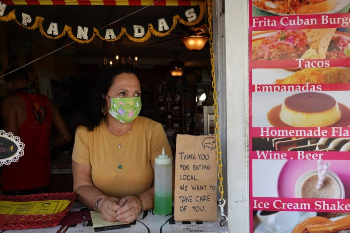Martia Weaver waits for customers at the window of her Freitas cuban burgers restaurant as the city government takes action to fight the coronavirus epidemic March 25, 2020 in Key West, Florida. Most tourists have left Key West because the city has closed hotels or short-term vacation rentals and asked restaurants to serve only take-out. Beaches and parks have been closed and starting Friday, non-residents cannot enter the Florida Keys without proof of employment or ownership as city officials attempt to contain COVID-19.