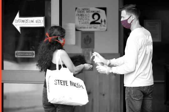 A store associate distributes hand sanitizer to customers entering Trader Joe's store in South Beach on April 14, 2020 in Miami Beach, Florida. The city of Miami Beach has put in place an emergency measure requiring all customers and employees of grocery stores, restaurants and pharmacies to wear face covers to help fight the COVID-19 pandemic.