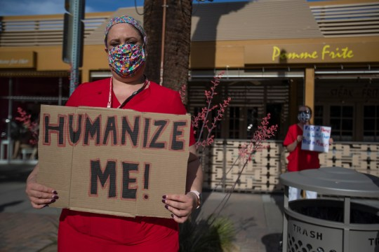Counter-protesters to opponents of the Stay at Home order gather to voice their opposition to downtown Palm Springs on April 26, 2020. The Stay at Home order has been put in place by the government of the state to prevent the spread of COVID -19 which killed more than 50,000 people in the United States as of April 26, 2020. Opponents invoke their constitutional right to an open economy.