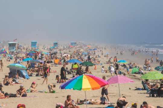 People enjoy the beach amid the new coronavirus pandemic in Huntington Beach, California on April 25, 2020.
