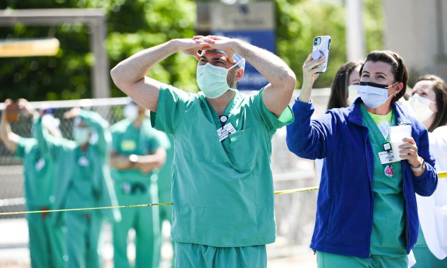 AnMed Health staff and bystanders take photos and video of F-16 planes from The South Carolina Air National Guard 169th Fighter Wing flying over the hospital in Anderson, S.C. Monday, April 27, 2020. The group stated they