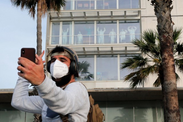 A man takes a selfie photo with healthcare workers in protective suits at the Hospital del Mar in Barcelona, encouraging people who exercise outside, early on May 2, 2020, during the hours allowed by the government to exercise, for the first time since the beginning of a national lockdown to prevent the spread of the COVID-19 disease.