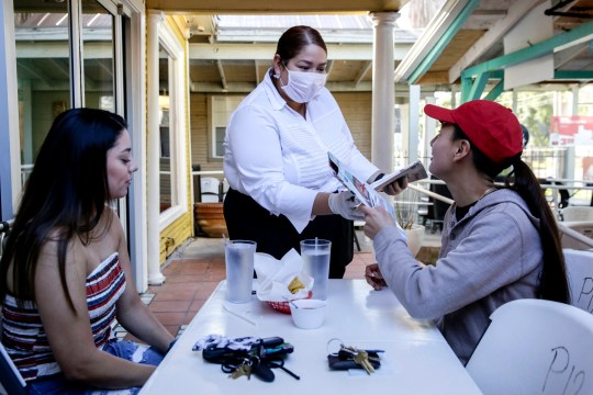 Dayana Solia takes client menus from Lexie Belche, left, and Aleza Ruiz to Juan in a Million on East Cesar Chavez Street in Austin, Texas, May 1. Ruiz called the restaurant at 7 a.m. to see if it was open after Governor Greg Abbott ordered the gradual reopening of Texas businesses amid the coronavirus epidemic. All retail stores, shopping centers, restaurants, cinemas, libraries and museums must limit customers to 25% of their listed occupancy.