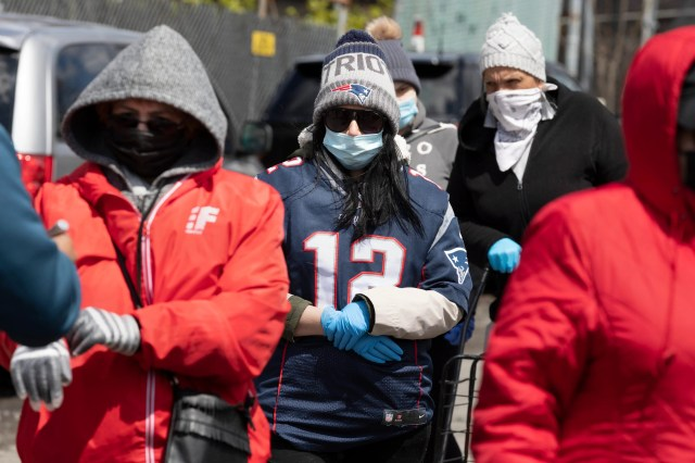 A woman dressed in a former New England Patriots' Tom Brady jersey, waits in line at a food distribution site, Saturday, May 9, 2020, in Chelsea, Mass. The donated food was delivered to the site in the Patriots' team truck.