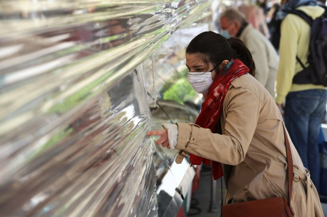 A shopper wearing a face mask points to products from behind a plastic sheet at a street market on May 14, 2020, on the Saxe Avenue in Paris, as France eases lockdown measures taken to curb the spread of the COVID-19 pandemic, caused by the novel coronavirus.