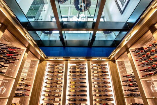 The lower level wine cellar has a glass ceiling overlooking the dining room. Maybe it allows the host to check wine choices with guests.