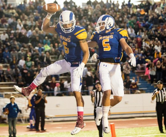 Dakarai Pecikonis from Angelo State University (left) and his teammate, Brett Rasberry, celebrate in the final zone after Pecikonis made a catch for a touchdown during the fight against Texas A & M-Commerce on October 11, 2014.