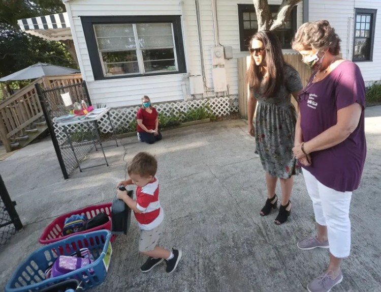 Sasha Staton talks with Kim Vukelja, owner and director of the Imagination Station child care center, while Nash Staton, 3, puts his lunchbox in his class's basket. Many women, including domestic abuse survivors, are struggling to pay for child care during the COVID-19 pandemic.