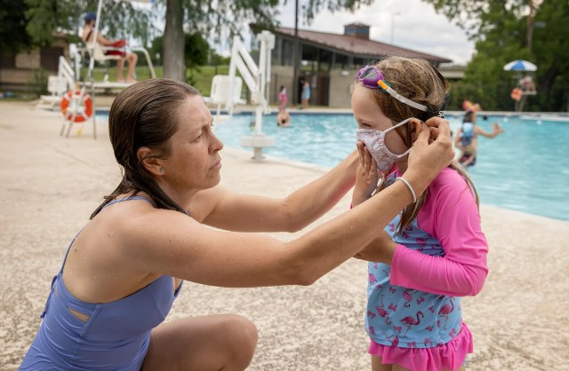 USA; Amanda Davidson helps her daughter, Lyle, put on her face mask after they got out of the pool at Rosewood Pool on Tuesday June 2, 2020. Some city-owned swimming pools are reopening with reduced hours and capacity and with new rules to slow the spread of the coronavirus. Guests must have their temperature taken and give their contact information before entering the facility, and they must wear face masks when outside the pool. The pool closes every two hours for a 15-minute cleaning and disinfecting.
