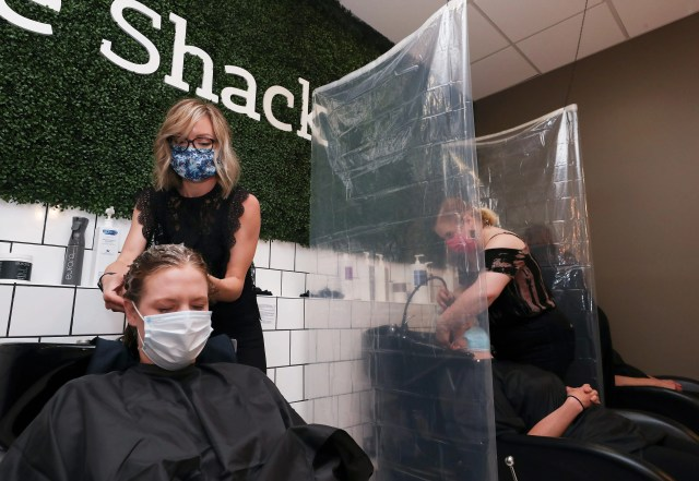 Stylist Rachel Carter washes reporter Maggie Menderski's hair at the Neatbeat hair salon in Louisville, Ky. on May 27, 2020. They are separated from other clients by newly installed plastic dividers. Salons have recently reopened following the shutdown due to the COVID-19 pandemic.