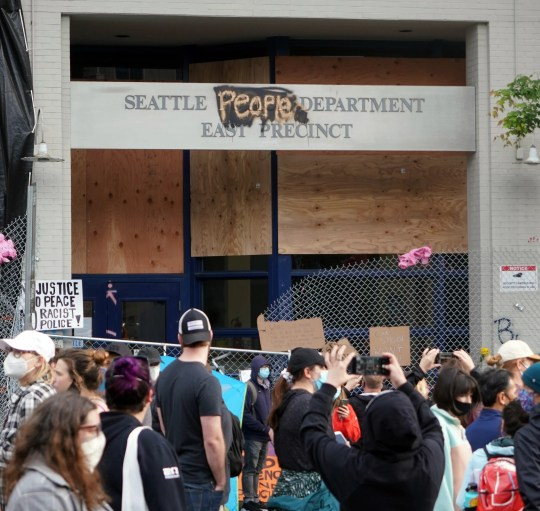 People take pictures of the Seattle Police Department's East Precinct building, which was renamed the Seattle People Department, during protests following the death of George Floyd in Minneapolis.