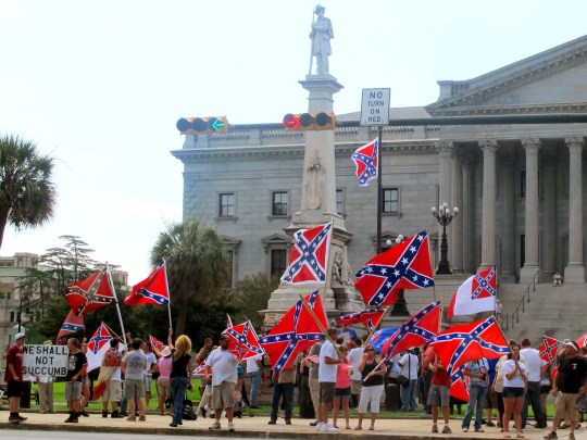 In this June 27, 2015 photo, supporters of keeping the Confederate battle flag flying at a Confederate monument at the South Carolina Statehouse wave flags during a rally in front of the statehouse in Columbia, South Carolina.