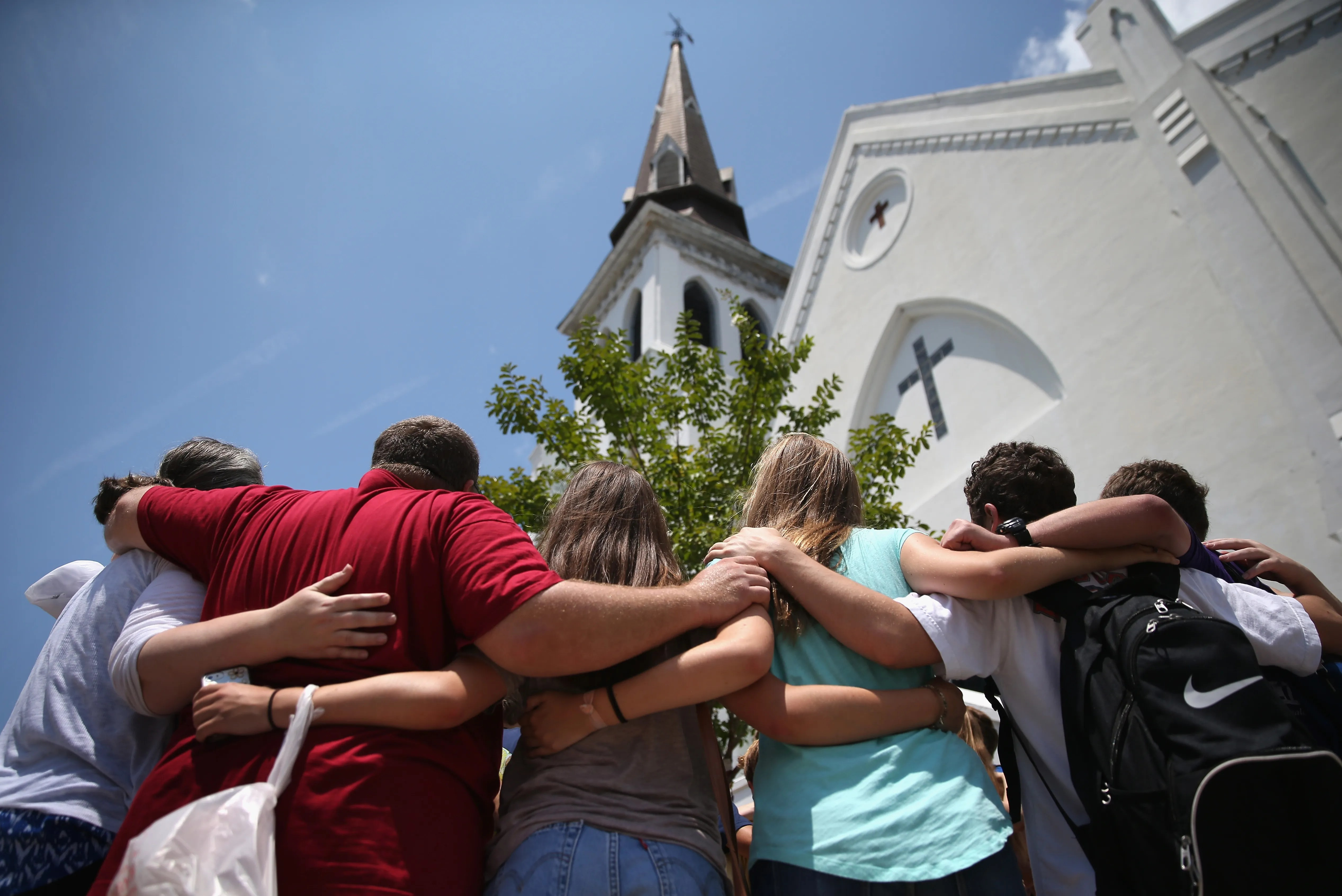 """A church youth group from Douthan, Ala., prays in front of the Emanuel AME Church in July 2015, a month after a mass shooting in Charleston, S.C. Visitors gathered at a makeshift shrine in front of the church in a show of faith and solidarity with """"Mother Emanuel,"""" as the church is known. Nine people were killed by white supremacist Dylann Roof, who was sentenced to death for the murders."""