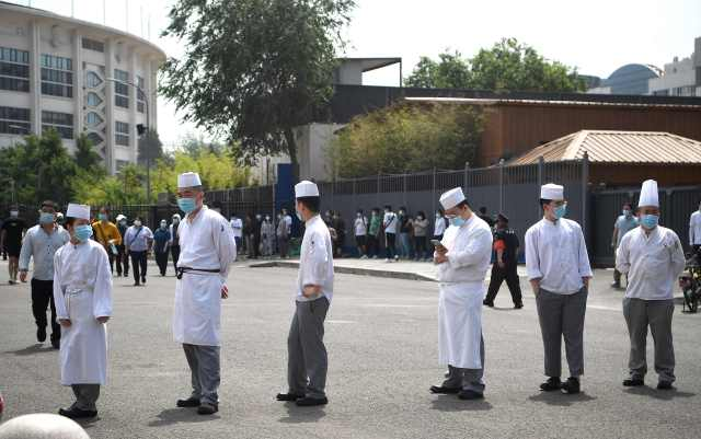 Chefs social distance while waiting to take a swab test for the COVID-19 coronavirus as officials conduct mass testing following a new cluster of cases last week, in Beijing on June 18, 2020. Beijing reported another 21 cases of the coronavirus on June 18, as authorities rushed to contain a new outbreak in the capital and warned cases may keep rising.