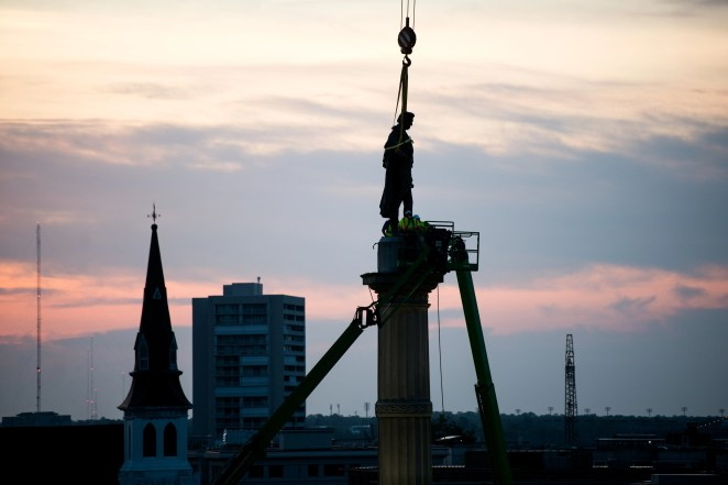 Workers use cherry pickers to access the statue of John C. Calhoun atop the monument in his honor at Marion Square on June 24, 2020 in Charleston, South Carolina. Work crews began dismantling the monument in Tuesday evening.