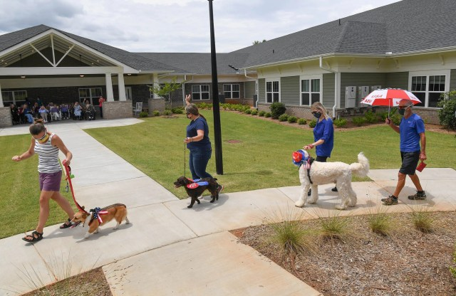 Participants Amy Saylor, left, leads her dog Josie during the Clemson Area PUP parade at Clemson Heritage Assisted Living in Central, S.C. Tuesday, June 30, 2020. A group of dogs led by Paws 2 Care of Greenville dressed in patriotic attire for a group of residents seated outdoors in the shade, and wished them a Happy Fourth of July.