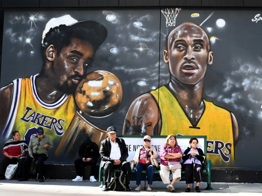 Feb 24, 2020; Los Angeles, California, USA; Residents wait for a bus with a mural of Kobe Bryant painted on the wall behind them in Koreatown. Today was the celebration of life for Kobe Bryant and daughter Gianna Bryant at Staples Center. Mandatory Credit: Jayne Kamin-Oncea-USA TODAY Sports