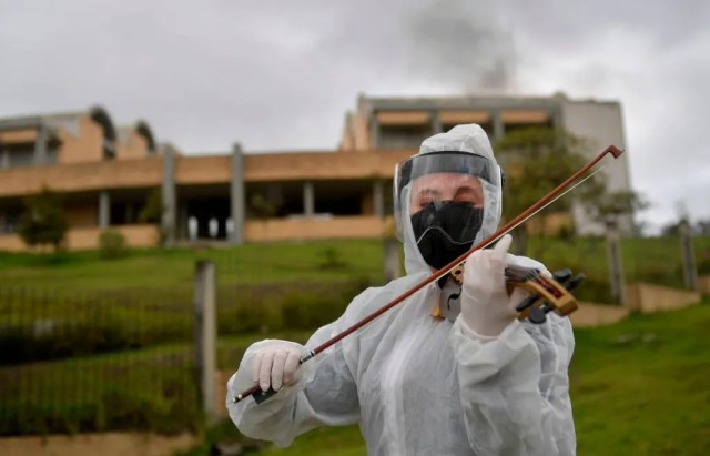 An employee of a funeral home plays the violin during the accompaniment of mourning before the cremation of a victim of the novel coronavirus COVID-19, at the Serafin cemetery in Bogota, on July 17, 2020. - The pandemic has killed at least 590,000 people worldwide, including more than 6,000 in Colombia, since it surfaced in China late last year and more than 13.8 million have been infected, according to an AFP tally at 1200 GMT on Friday based on official sources.