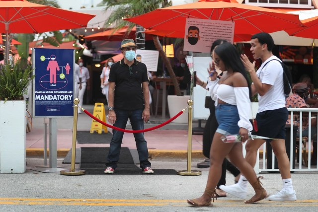 Juan Carlos, a host at Ocean 10 restaurant, stands at the entrance of the restaurant to turn customers away as a curfew from 8pm to 6am is put in place on July 18, 2020 in Miami Beach, Florida. The City of Miami Beach put the curfew back into place to fight the spread of the coronavirus (COVID-19), which has spiked in recent days after the reopening of businesses.