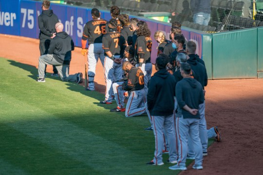 Several members of the San Francisco Giants kneel before the national anthem before Monday's exhibition game against the Oakland Athletics.