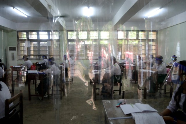 Students seen through a plastic curtain placed on a doorway attending classes during the first day of reopening of public high schools following closure due to the COVID-19 coronavirus in Yangon on July 21, 2020.