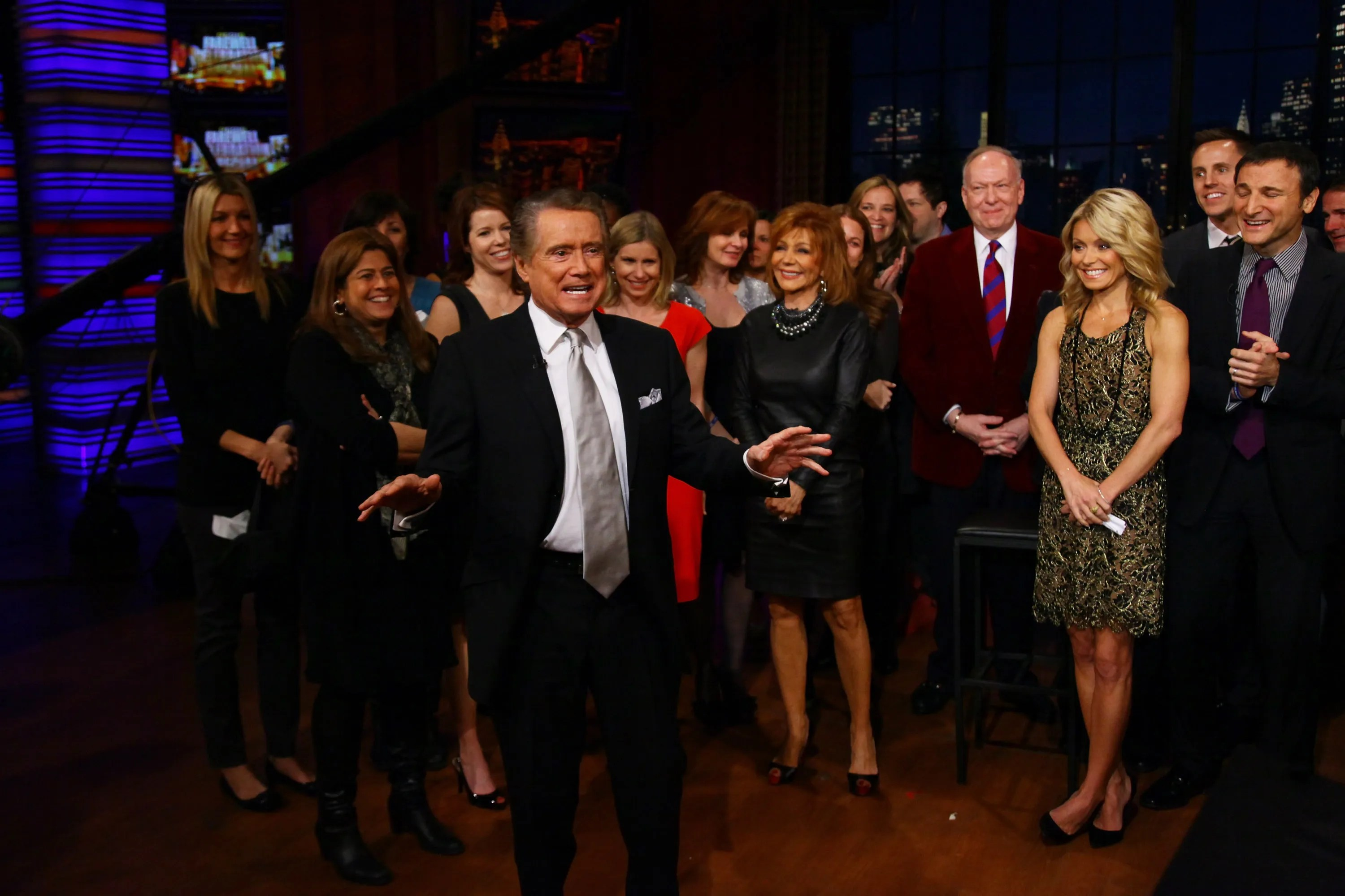 """Regis Philbin, center, and Kelly Ripa, right, on the set during Philbin's final show of """"Live! With Regis and Kelly"""" on Nov. 18, 2011, in New York."""
