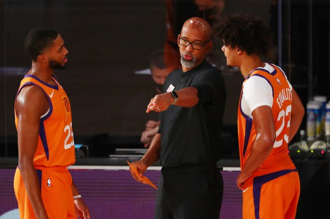 Jul 31, 2020; Lake Buena Vista, Florida, USA;  Phoenix Suns head coach Monty Williams talks with forward Cameron Johnson (23) and forward Mikal Bridges (25) against the Washington Wizards in the second half of a NBA basketball game in the Visa Athletic Center at the ESPN Wide World of Sports Complex. Mandatory Credit: Kim Klement-USA TODAY Sports