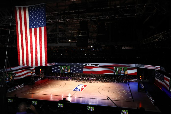 July 30: Lakers and Clippers players and coaches wear Black Lives Matter shirts and kneel during the national anthem.