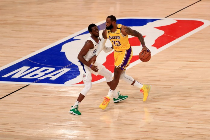 July 30: Lakers forward LeBron James (23) brings the ball up the court against Clippers defender Reggie Jackson (1).