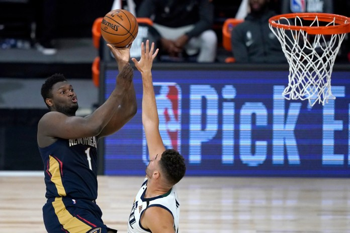 July 30: Pelicans forward Zion Williamson (1) shoots over Jazz defender Georges Niang.