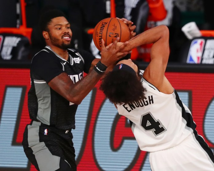 July 31: Kings guard Kent Bazemore (26) fights for a loose ball against Spurs guard Derrick White (4).