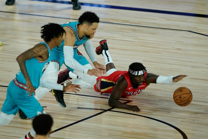Aug. 3: Pelicans guard Jrue Holiday dives for a loose ball against Grizzlies guard Dillon Brooks