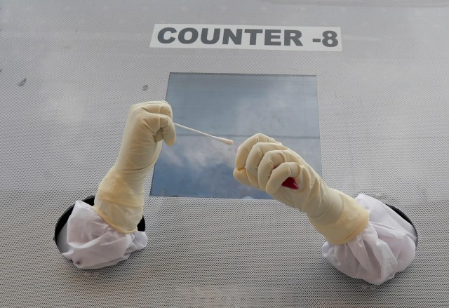 A health worker prepares to collect nasal swab samples for COVID-19 tests at a mobile testing centre in Hyderabad, India, July 31, 2020. India is the third hardest-hit country by the pandemic in the world after the United States and Brazil.