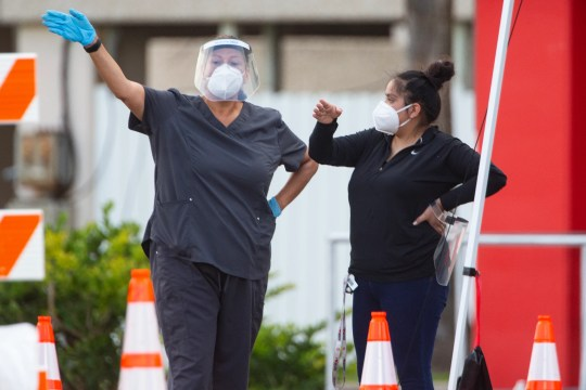 Healthcare workers conduct COVID-19 testing in the parking lot at the American Bank Center on Thursday, Aug. 6, 2020.