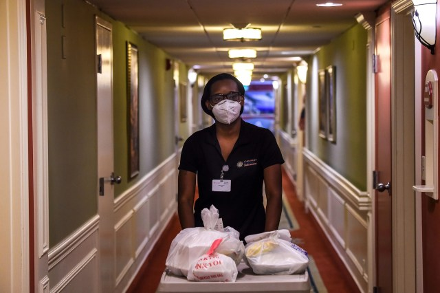 Shanika Williams wears a facemask as she delivers food in John Knox Village, a retirement community in Pompano Beach some 40 miles north of Miami, Fla. on Aug. 7, 2020. About 900 retirees live in the John Knox Village senior community in Pompano Beach, South Florida. Of these, about 400 have learned to use technology to order food to their apartments, communicate with each other or participate in online social activities.